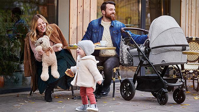 Famiglia che ride seduta al bar all'aperto. La mamma mostra alla bambina un giocattolo e il padre guarda l'altro bambino sdraiato sul passeggino di Kinderkraft.